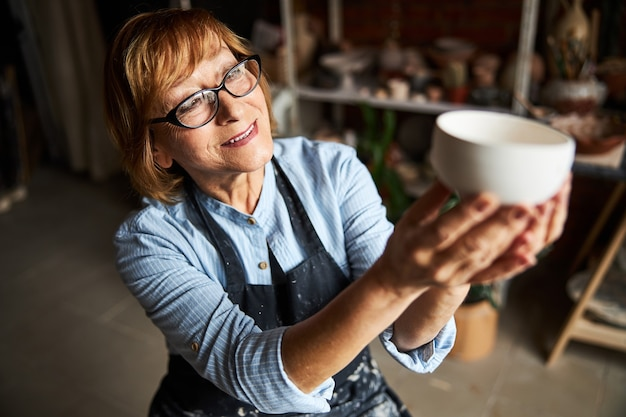 Bella donna anziana artista di ceramica che tiene una ciotola di terracotta fatta a mano e sorridente mentre lavora nello studio di ceramica