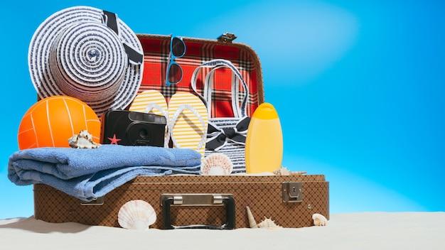 Bella valigia aperta piena di sabbia bianca e varie cose per il viaggio in spiaggia in piedi su sfondo blu