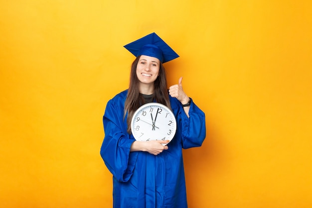 Una bella foto di uno studente allegro con in mano un grande orologio bianco vestito con un'uniforme da laurea vicino a un muro giallo