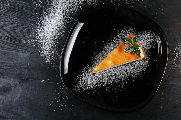 Una bella foto di un pezzo di torta su un piatto in polvere nera