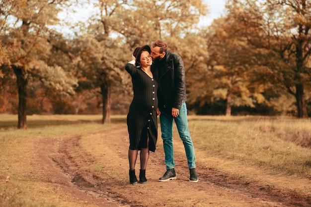 Bella foto di una giovane famiglia nel parco del marito che bacia sulla guancia la moglie incinta