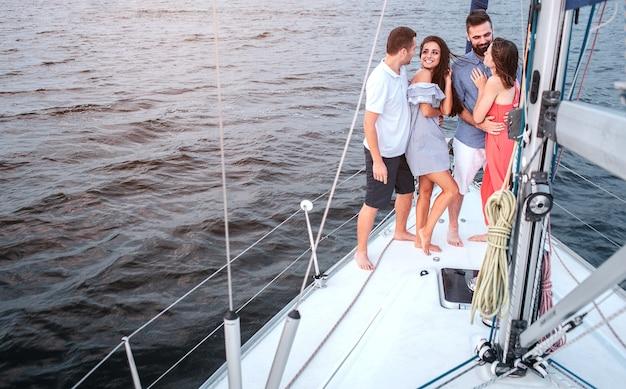 Bella foto di quattro persone in piedi su uno yacht. la bruna sta guardando il ragazzo.