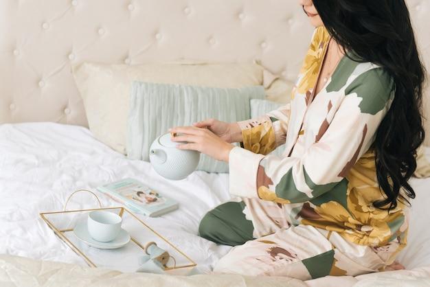 Bella foto di una ragazza incinta. ragazza che mangia prima colazione a letto