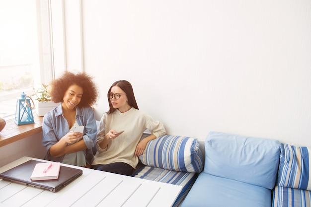 Bella foto di studenti seduti vicini l'uno all'altro sul divano. tengono in mano i telefoni. la ragazza afroamericana sorride mentre i suoi amici non sono felici e si chiedono. ora hanno una pausa.