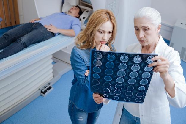 Bella donna interessata piacevole in piedi vicino al medico e guardando l'immagine a raggi x mentre si preoccupa per suo marito