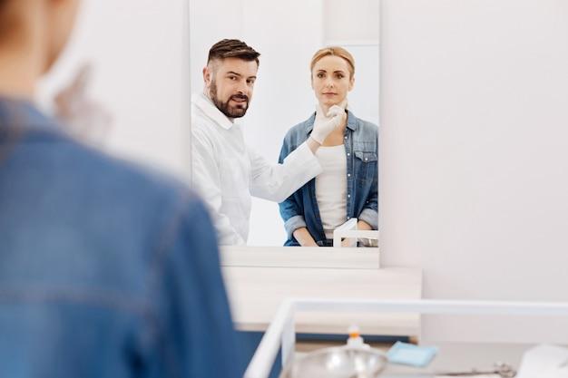 Simpatico chirurgo estetico piacevole che si guarda allo specchio e sorride e indica il mento dei suoi pazienti