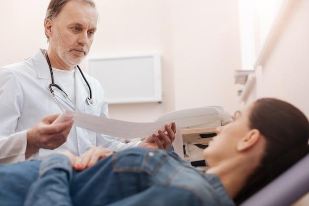 Simpatico e simpatico cardiologo qualificato che spiega la diagnosi dopo aver studiato cardiogramma femminile e indicato alcune patologie