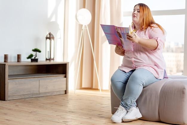 Bella donna grassoccia che mangia una gustosa banana mentre legge una rivista