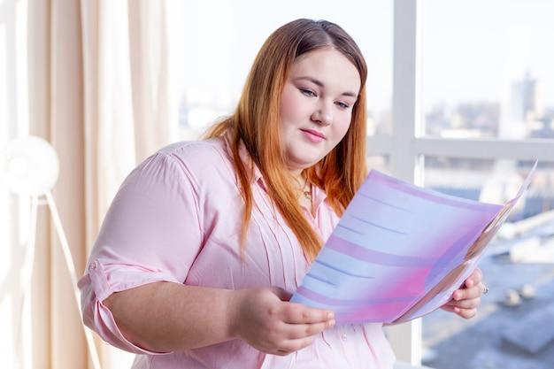 Bella donna grassoccia che legge una rivista interessante mentre vuole essere bella