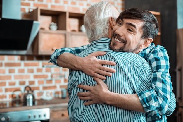 Bel uomo gioioso positivo che sorride e abbraccia suo padre mentre gli esprime il suo amore