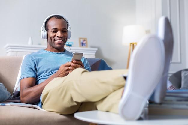 Bel uomo gioioso positivo che indossa le cuffie e guardando il suo smartphone mentre si ascolta la musica