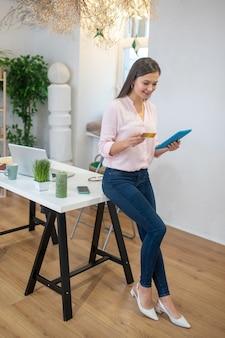 Bella donna positiva che inserisce il numero della sua carta di credito mentre effettua un pagamento online