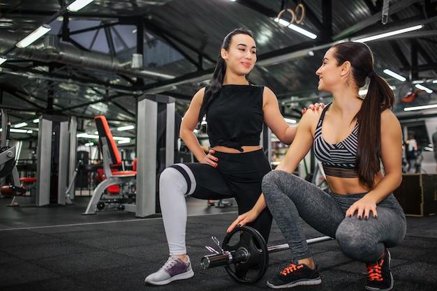 La giovane donna asiatica piacevole e positiva sta su un ginocchio e guarda la sua amica.