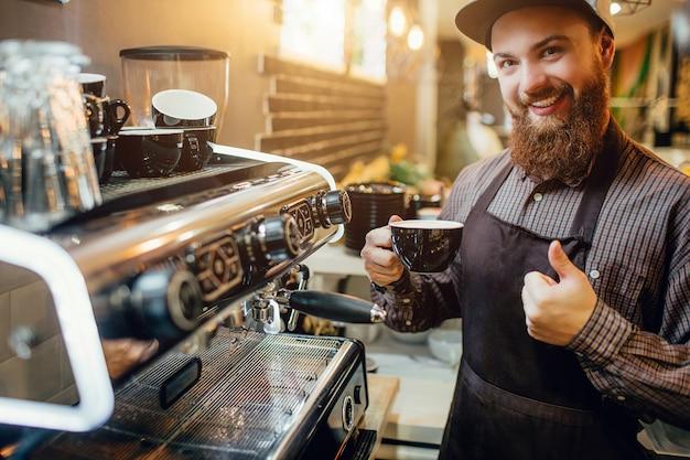 Bel giovane e positivo barusta in cucina. tiene il pollice grande e la tazza di caffè. guy sorride alla telecamera.