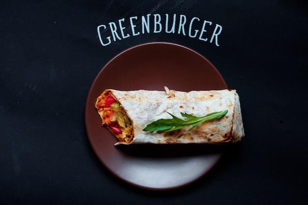 Bello e pronto da mangiare shaurma o panino con pomodori tagliati a metà nelle vicinanze, greenburger con vista dall'alto?
