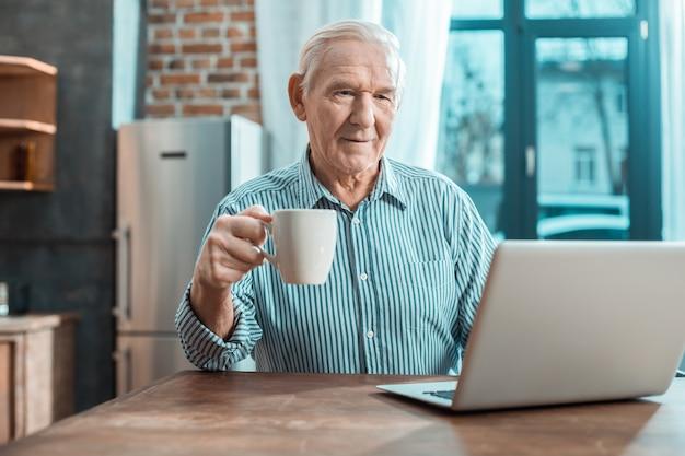 Bel uomo anziano rilassato prendendo il tè e guardando lo schermo del laptop mentre si riposa a casa