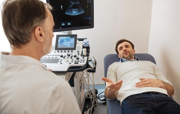 Simpatico paziente responsabile e preoccupato che fa visita all'ospedale e condivide le sue preoccupazioni con il medico prima di eseguire una procedura ecografica