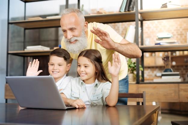 Felice di vederti. bell'uomo anziano in piedi dietro i suoi nipotini seduti al tavolo e facendo una videochiamata mentre tutti loro salutano la webcam