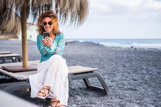 Bel sorriso bella donna solitaria di mezza età godersi la spiaggia seduta su un sedile con l'oceano. utilizzando lo smartphone per connettersi con gli amici a casa o per lavorare con un business online di squadra.