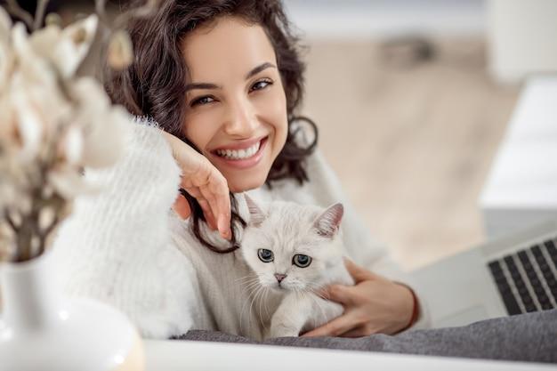 Bel sorriso. giovane donna sveglia che tiene un gatto bianco e che sorride piacevolmente