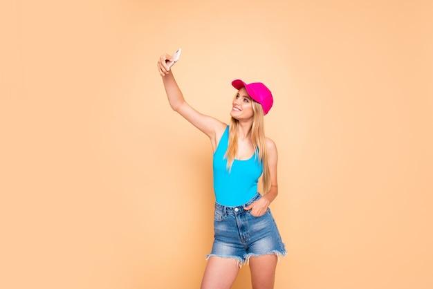 Bella ragazza sorridente che indossa pantaloncini di jeans, berretto rosa e che fa foto di sé con il telefono