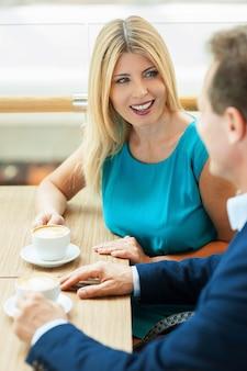 Bella chiacchierata. bella coppia matura che beve caffè e si parla mentre è seduta in una caffetteria
