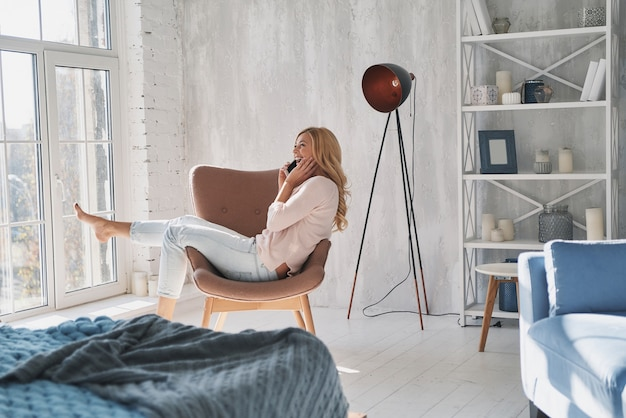 Bella chiacchierata con il fidanzato. bella giovane donna che parla sul suo smartphone e sorride mentre è seduta in poltrona vicino alla finestra di casa