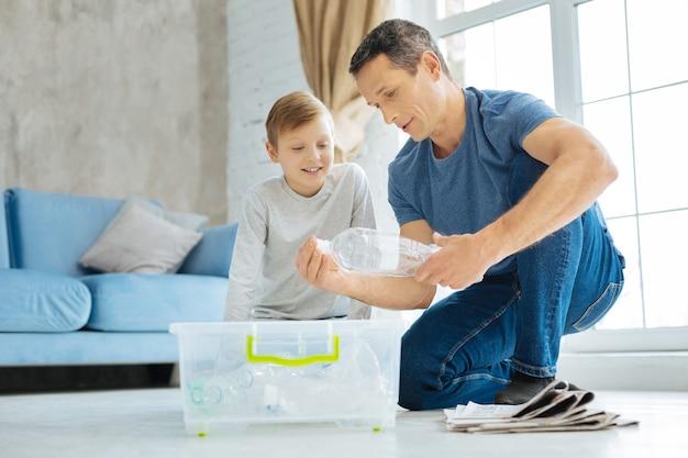 Brava insegnante. piacevole e premuroso giovane padre seduto sul tavolo accanto a suo figlio e mostrandogli come schiacciare la bottiglia di plastica prima di riciclarla