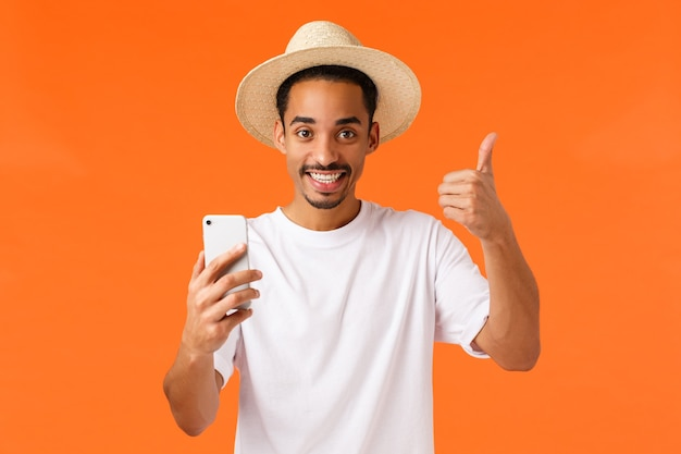 Bene grazie. felice turista maschio afroamericano ha chiesto al direttore dell'hotel di fornire la password wifi per contattare la famiglia tramite videochiamata, mostrare il pollice in su, rilassarsi durante le vacanze, località di villeggiatura estiva, sfondo arancione.