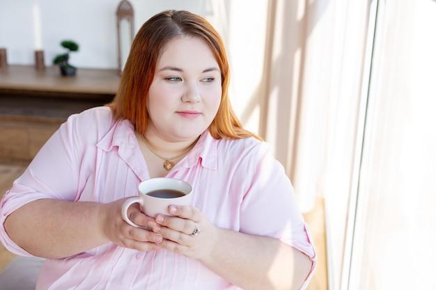 Bella donna premurosa che tiene una tazza di tè mentre è seduta vicino alla finestra