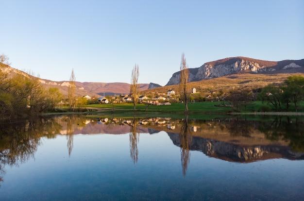Bel villaggio sulla riva di un lago di montagna sogna la vita nella natura lontano dalla civiltà e dalle grandi città