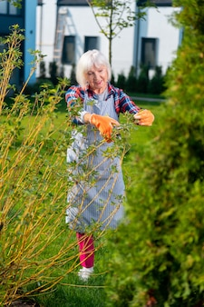 Bel tempo. bella donna coinvolta che si sente motivata mentre lavora in giardino