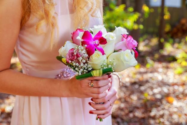 Un bel bouquet da sposa di viola, rosa e bianco tenuto da una sposa