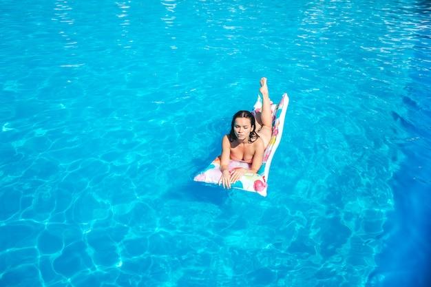 Una ragazza carina e ben costruita giace sul materasso ad aria e si abbronza dal sole. lei è seria e concentrata. la ragazza ha un po 'di riposo.