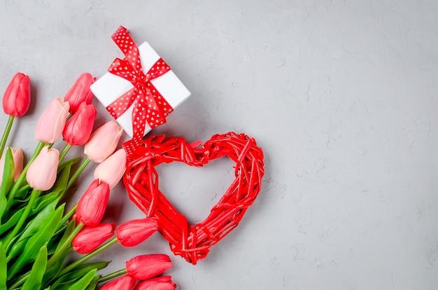 Bel cuore rosso di vimini con confezione regalo e tulipani rossi su sfondo grigio vecchio.