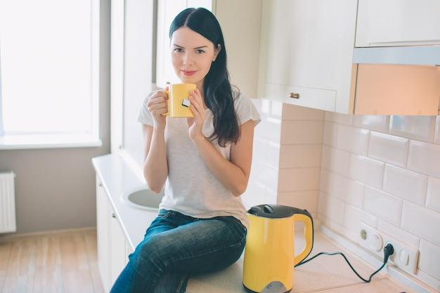 Bella donna si siede sul marciapiede con una tazza in mano.
