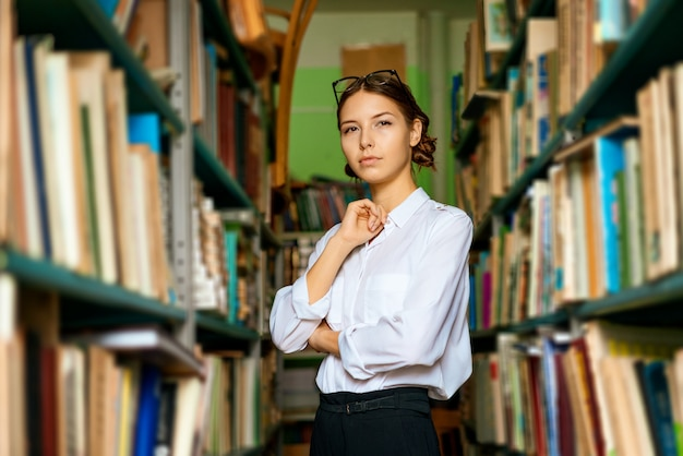 Una bella donna con una camicia bianca in biblioteca sorride