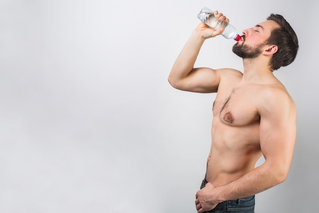 Bella e meravigliosa foto di un bell'uomo in piedi molto vicino a un muro bianco e bevendo un po 'd'acqua dalla bottiglia. si sta godendo il momento.