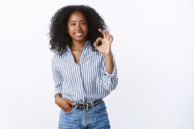 Bel lavoro, risultato fantastico. soddisfatto compiaciuto attraente sorridente donna afroamericana che mostra bene ok gesto ghignando felice servizio eccellente raccomandando, parere positivo affermativo