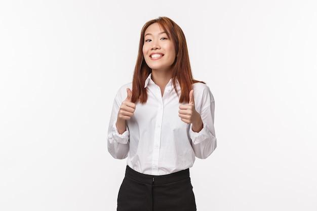 Bel lavoro, stai facendo un grande tesoro. ragazza asiatica allegra e incoraggiante che fa il tifo per la persona, mostra il pollice in su e sorride in segno di approvazione, dà una risposta positiva, accetta o piace qualcosa di buono