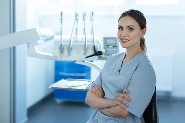 Bel posto di lavoro. affascinante giovane femmina dentista in posa nel suo ufficio e sorride alla telecamera mentre incrociando le braccia sul petto