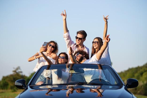 Belle ragazze e ragazzi con gli occhiali da sole sono seduti in una cabriolet nera sulla strada alzando le mani e facendo selfie in una giornata di sole. .