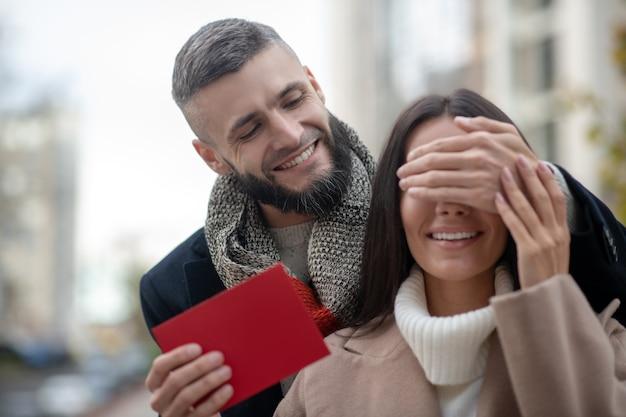 Bel giovane che copre gli occhi della sua ragazza mentre ha una sorpresa per lei