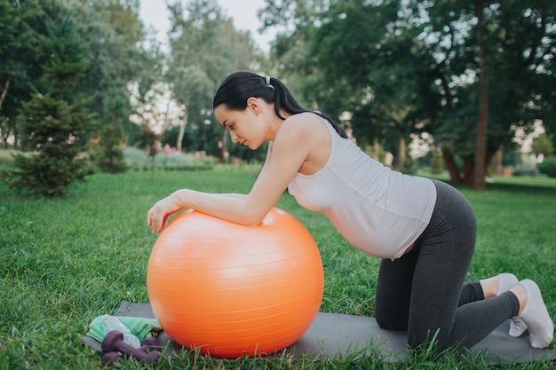 Giovane donna incinta piacevole che ha allenamento in parco. si alza in ginocchio e guarda in basso. modello inclinato a grande palla fitness arancione.