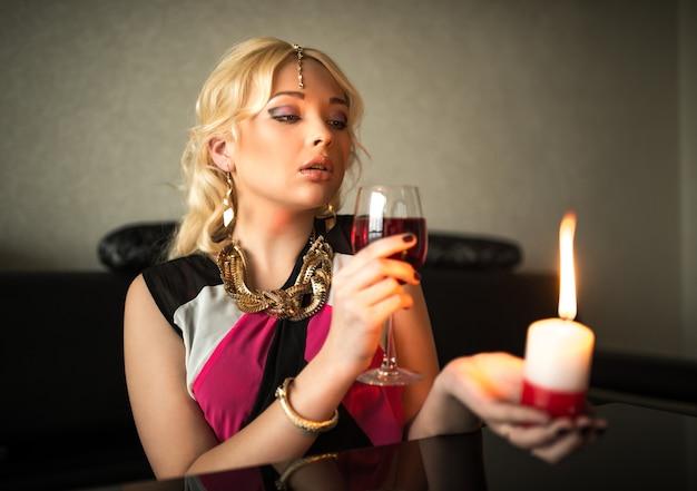Bella maga bionda giovane donna beve vino seduto a un tavolo circondato da candele