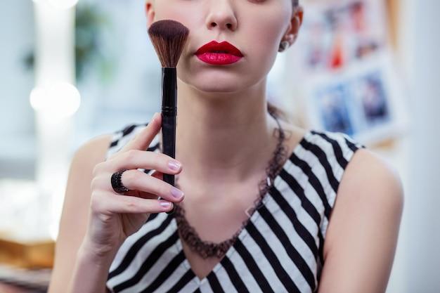 Bella giovane donna che tiene il suo pennello da trucco mentre ha le labbra rosse