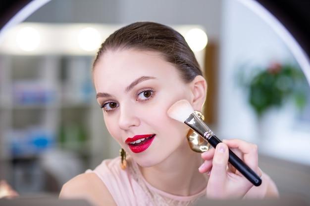 Bella giovane donna che si guarda il viso mentre indossa cosmetici decorativi