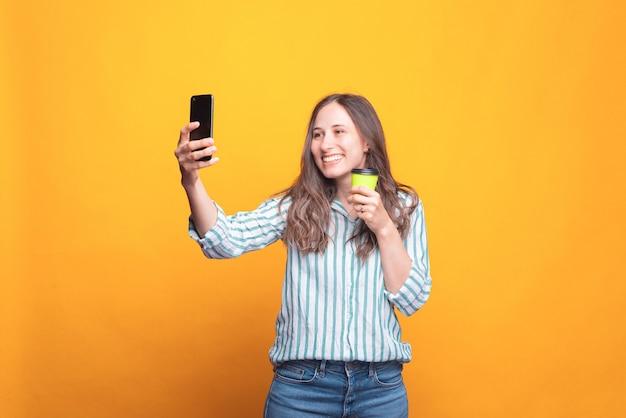 Bella giovane donna che prende un selfie e che tiene una tazza con una bevanda calda vicino a un muro giallo