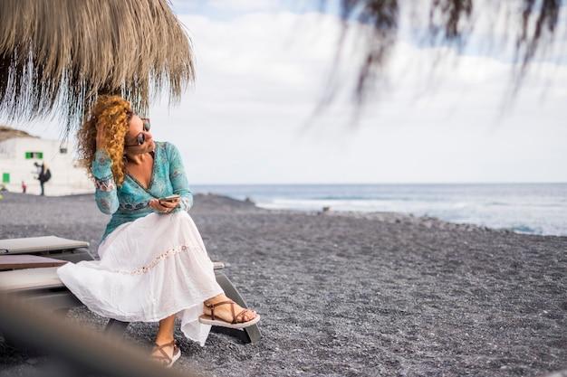 Bella giovane donna usa il telefono in spiaggia in attività di svago di vacanza in spiaggia. l'oceano e le onde sullo sfondo mentre si tocca i capelli castani ricci. occhiali da sole sul viso di bellezza