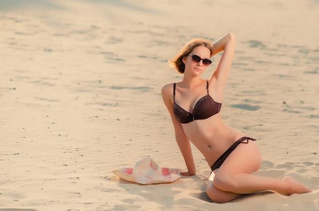 La giovane donna caucasica attraente elegante in bicchieri sulla spiaggia, è seduta sulla sabbia dorata. ricreazione e coccole in riva al mare (oceano, fiume, lago) in estate e nelle giornate di sole.